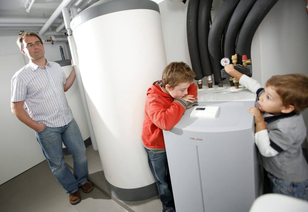 father and sons looking at heat pump
